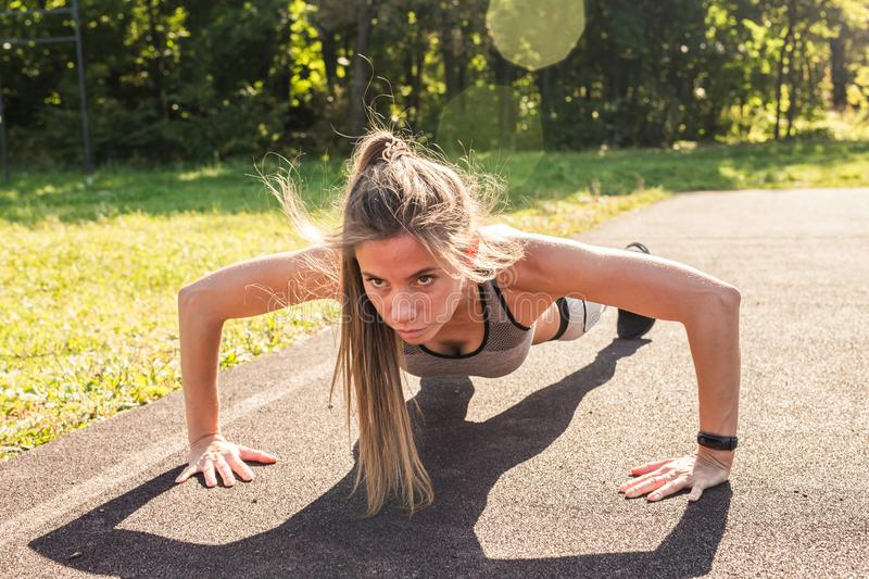 Fitness woman doing push-ups during outdoor cross training workout. Beautiful young and fit fitness sport model training royalty free stock image