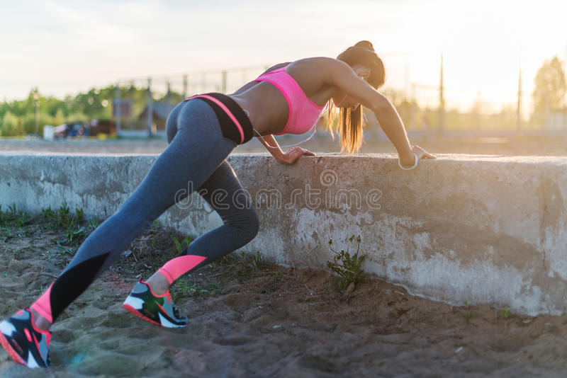 Fitness woman doing push ups Outdoor training workout summer evening. Concept sport healthy lifestyle. Fitness woman doing push ups Outdoor training workout stock image
