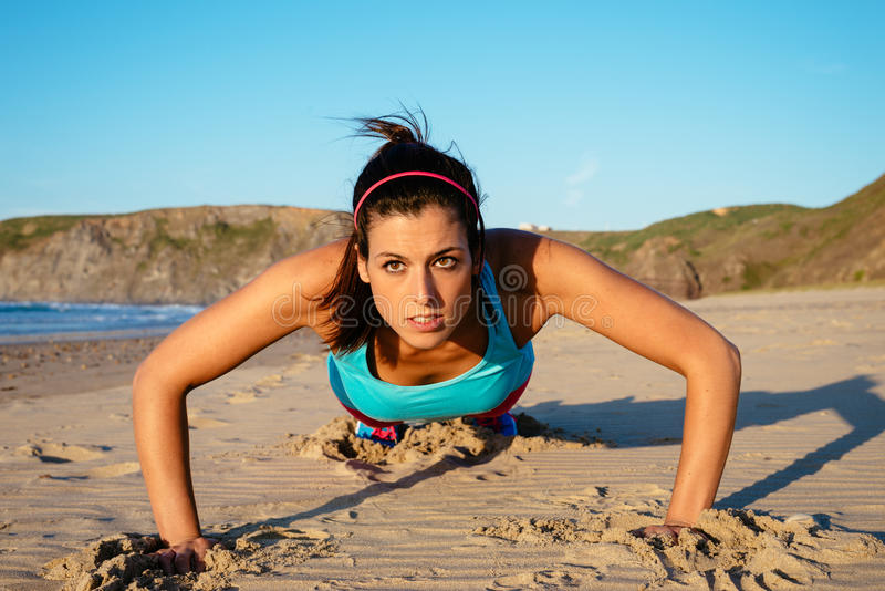 Fitness woman doing push ups workout. Fitness woman doing push ups at the beach on summer. Brunette sporty girl training hard royalty free stock photo