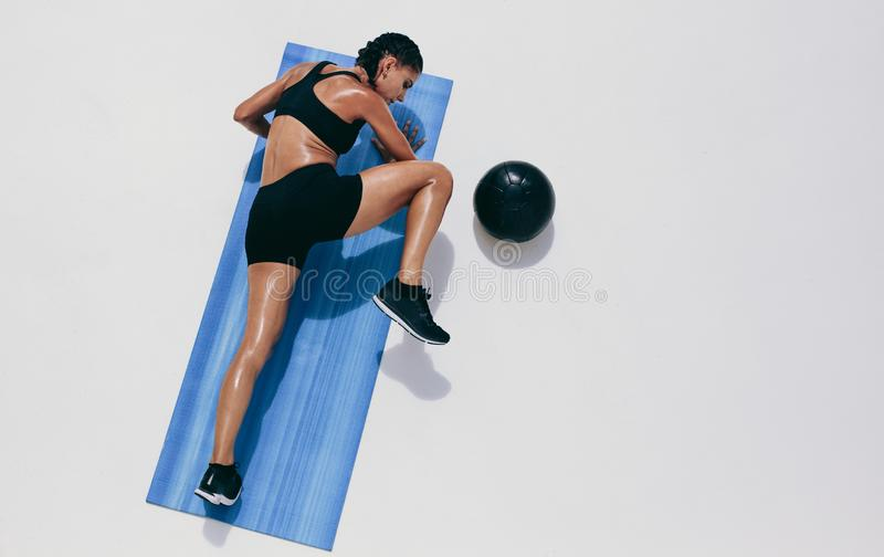 Fitness woman doing push ups on a yoga mat. Top view of a woman athlete doing fitness training with a medicine ball by her side. Fitness woman doing push ups stock photos