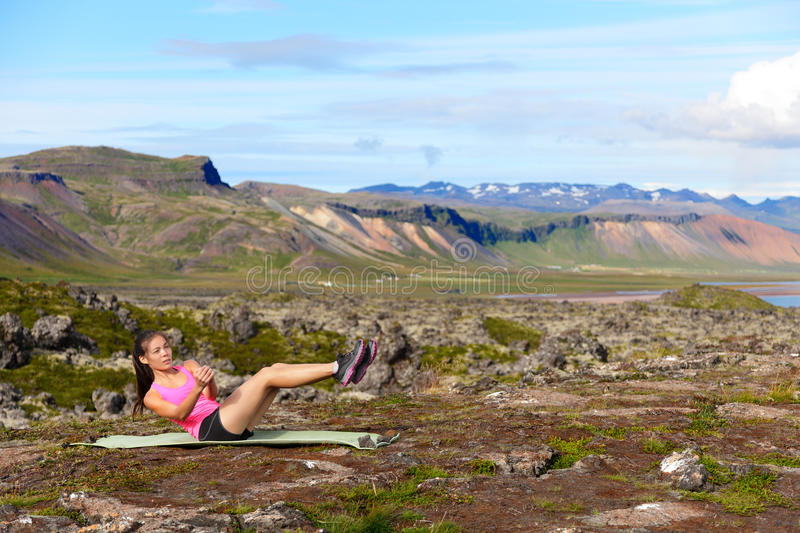 Fitness woman doing russian twist core exercise. Outside. Fit female training stomach in amazing nature landscape on Iceland. Fit female sport model girl royalty free stock images