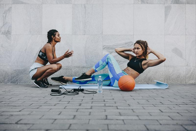 Fitness woman doing sit ups outdoors. Fitness women training outdoors sitting on exercise mat with skipping rope and basketball on the floor. Woman doing sit ups stock image
