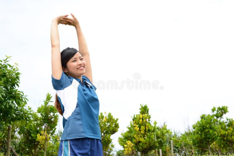 Fitness woman doing stretching exercise. Young woman relaxing at the park stock photo