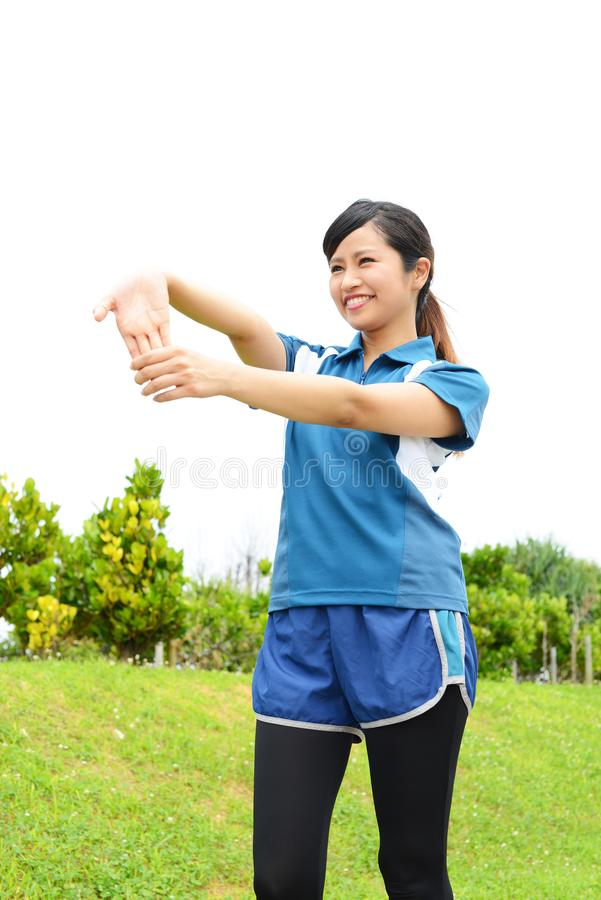 Fitness woman doing stretching exercise. Young woman relaxing at the park stock photography
