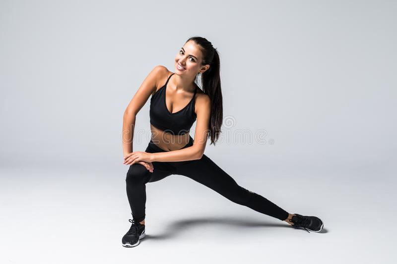 Fitness woman doing stretching legs workout. Full length shot of young woman on white background. Stretching and motivation royalty free stock photo