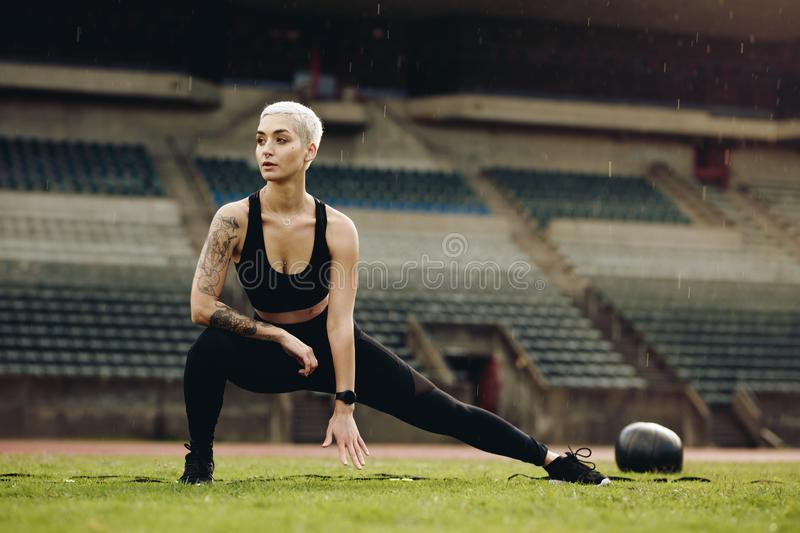 Fitness woman doing warm up exercises stretching her legs royalty free stock images