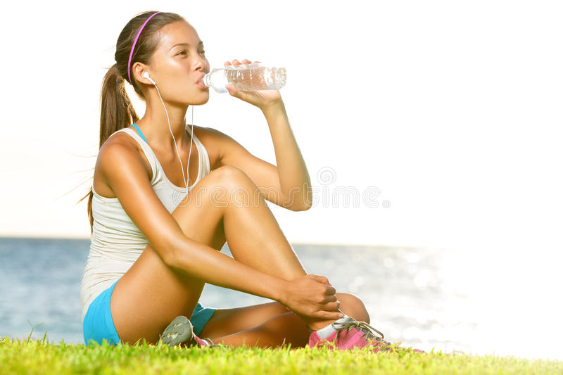 Fitness woman drinking water after workout outside royalty free stock image
