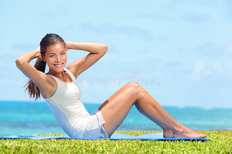 Fitness woman exercising doing sit ups outside. During crossfit exercise training. Happy fit girl doing side crunches situps smiling happy. Beautiful mixed race royalty free stock photography