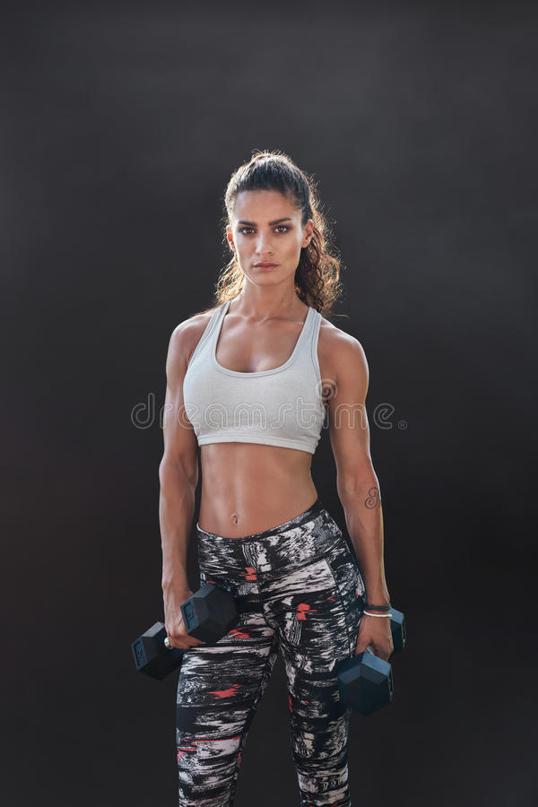 Fitness woman exercising with heavy weights. Fitness woman exercising with dumbbells. Beautiful fitness instructor on black background. Female model with stock images