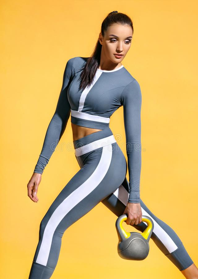Fitness woman in fashionable sportswear holding kettlebell on yellow background royalty free stock photos