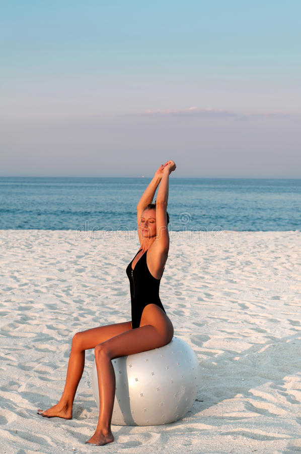 Fitness woman with fit ball on beach outdoors. Fitness girl in one-piece swimsuit work out with pilates ball at seaside royalty free stock photography