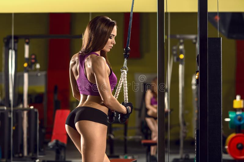 Fitness woman in gym. Young fitness woman in gym perform exercise with exercise machine, horizontal photo royalty free stock image