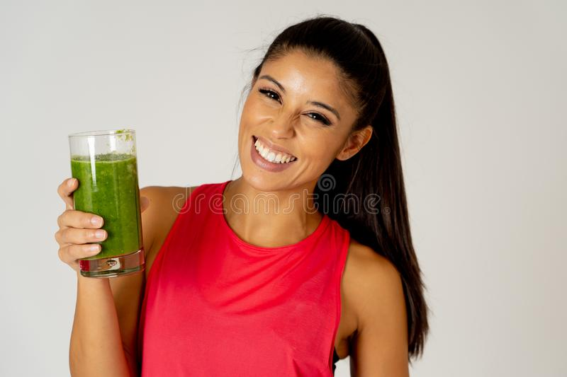 Happy beautiful fit sport woman smiling and drinking healthy fresh vegetable smoothie royalty free stock photo