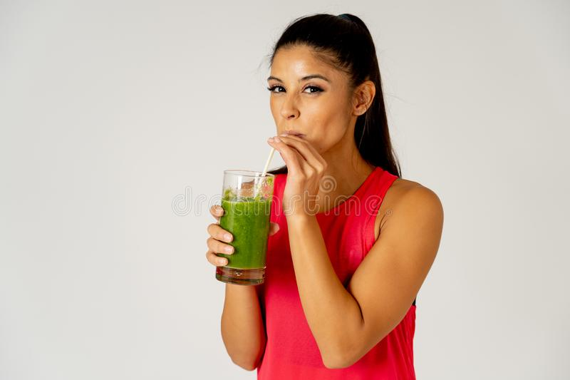 Happy beautiful fit sport woman smiling and drinking healthy fresh vegetable smoothie royalty free stock image