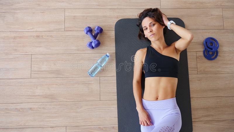 Fitness woman having rest, top view. Young girl lying on mat. Bodybuilding, healthy lifestyle concept. Copyspace royalty free stock photo