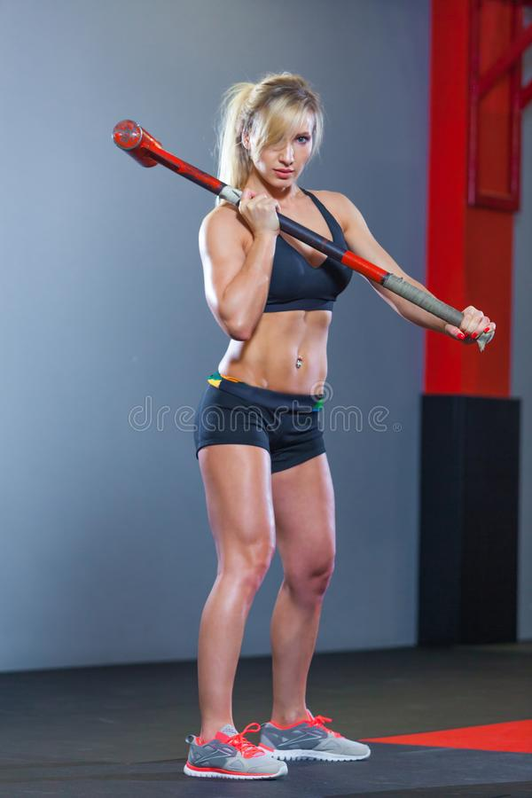 Fitness woman hitting wheel tire with hammer sledge in the gym. stock photos