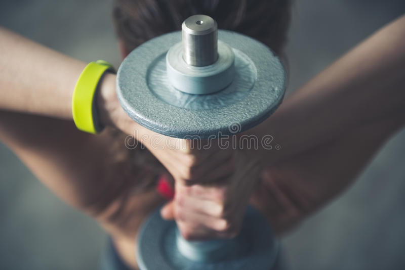 Fitness woman holding dumbbell behind head. Close up royalty free stock image