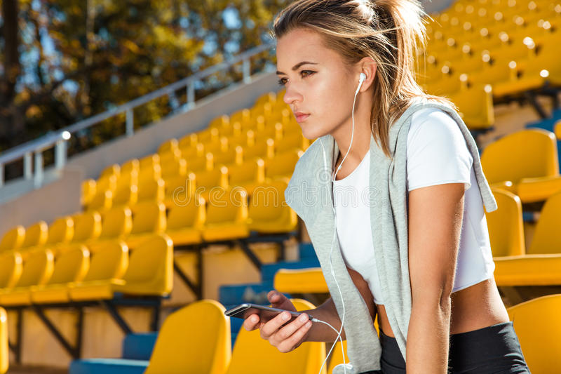 Fitness woman holding smartphone stock photography