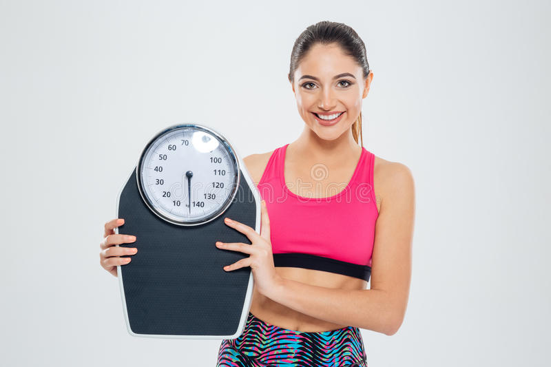 Fitness woman holding weighing machine. Happy fitness woman holding weighing machine isolated on a white background and looking at camera royalty free stock photos