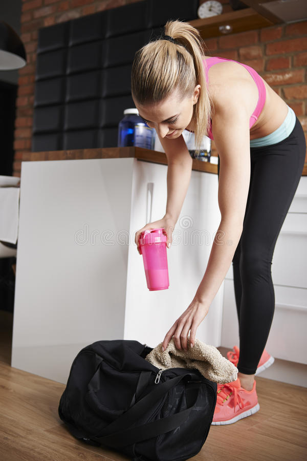 Fitness woman at home. Packing bag for the gym stock photography