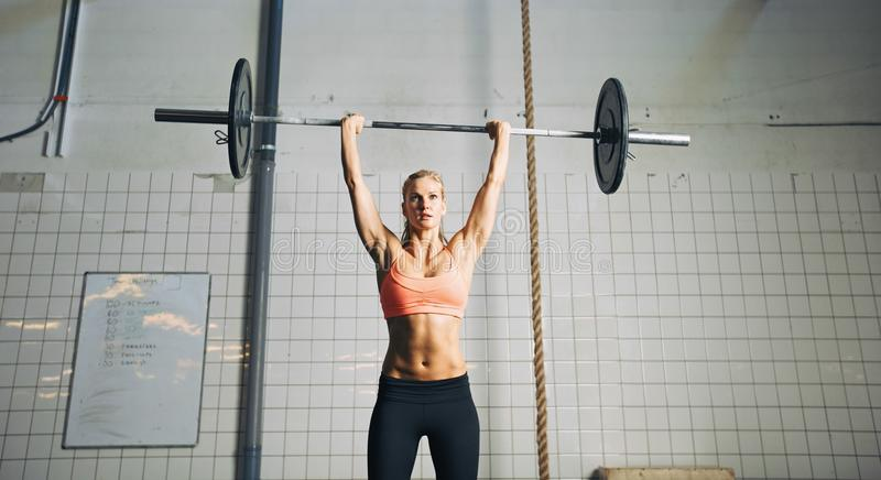 Fitness woman lifting barbells. Muscular young female athlete doing weightlifting at crossfit gym. Fit young woman model lifting heavy weights at gym royalty free stock image