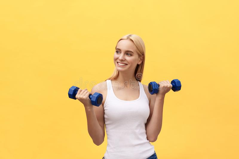 Fitness woman lifting weights smiling happy isolated on yellow background. Fit sporty Caucasian female fitness model. Fitness woman lifting weights smiling royalty free stock image