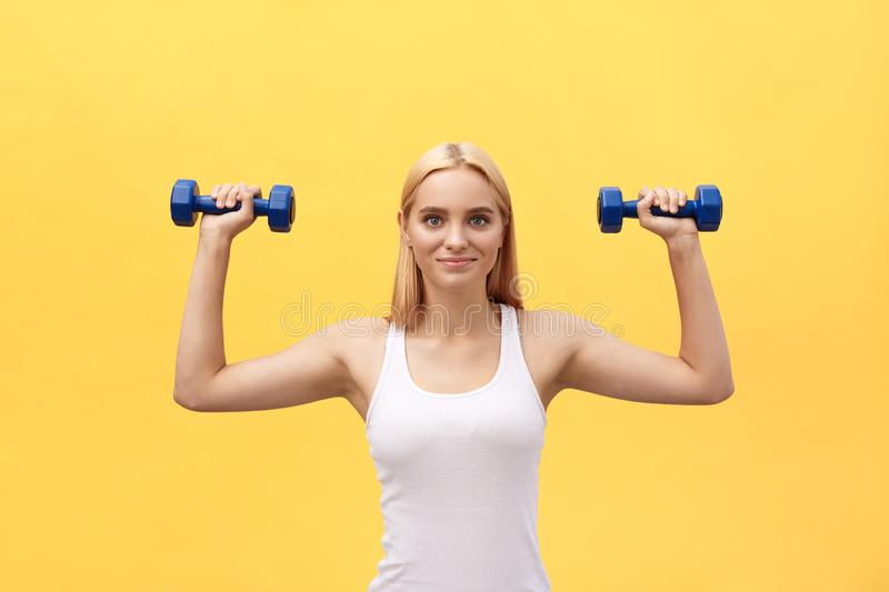 Fitness woman lifting weights smiling happy isolated on yellow background. Fit sporty Caucasian female fitness model. Fitness woman lifting weights smiling stock photography