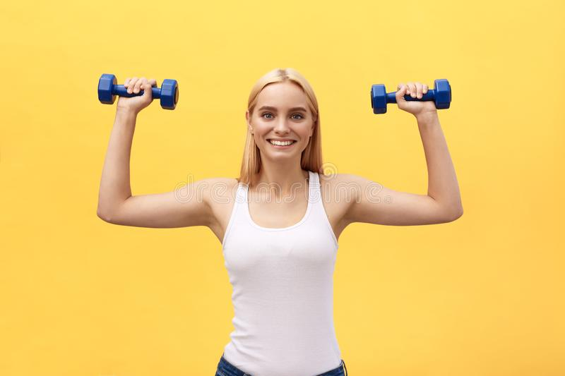 Fitness woman lifting weights smiling happy isolated on yellow background. Fit sporty Caucasian female fitness model. Fitness woman lifting weights smiling royalty free stock photo
