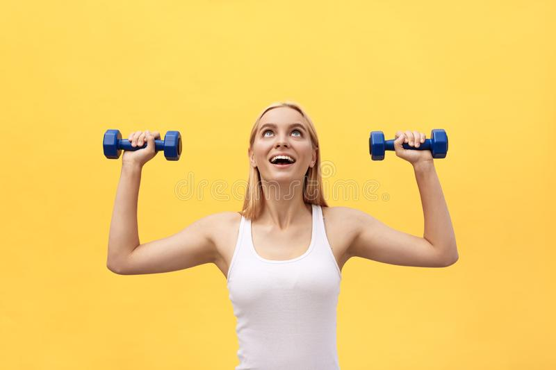 Fitness woman lifting weights smiling happy isolated on yellow background. Fit sporty Caucasian female fitness model. Fitness woman lifting weights smiling stock images