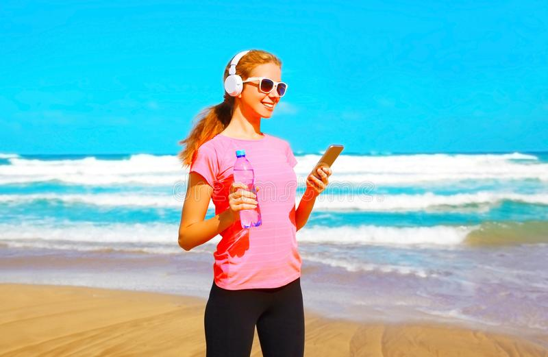 Fitness woman listens to music in wireless headphones with smartphone. On the beach stock images