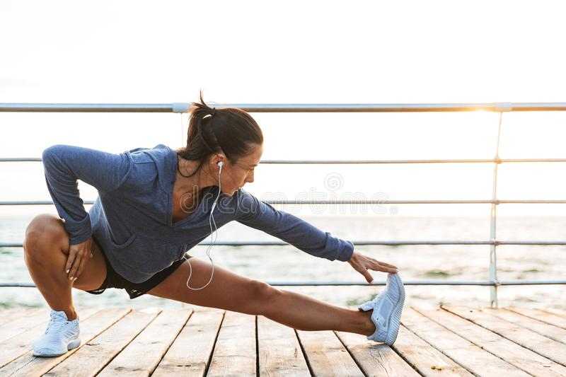 Fitness woman make stretching exercises at the beach outdoors listening music with earphones. Image of a beautiful young sports fitness woman make stretching royalty free stock photography