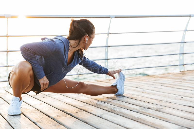 Fitness woman make stretching exercises at the beach outdoors listening music with earphones. Image of a beautiful young sports fitness woman make stretching stock photos