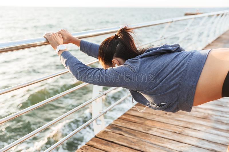 Fitness woman make stretching exercises at the beach outdoors listening music with earphones. Image of a beautiful young sports fitness woman make stretching royalty free stock image
