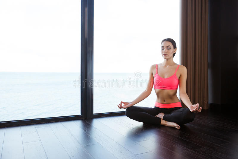 Fitness woman meditating in gym stock image