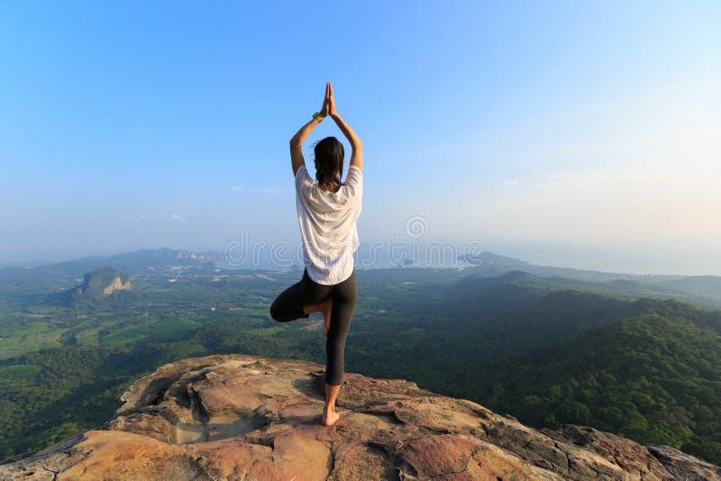Fitness woman meditating on mountain peak stock photos