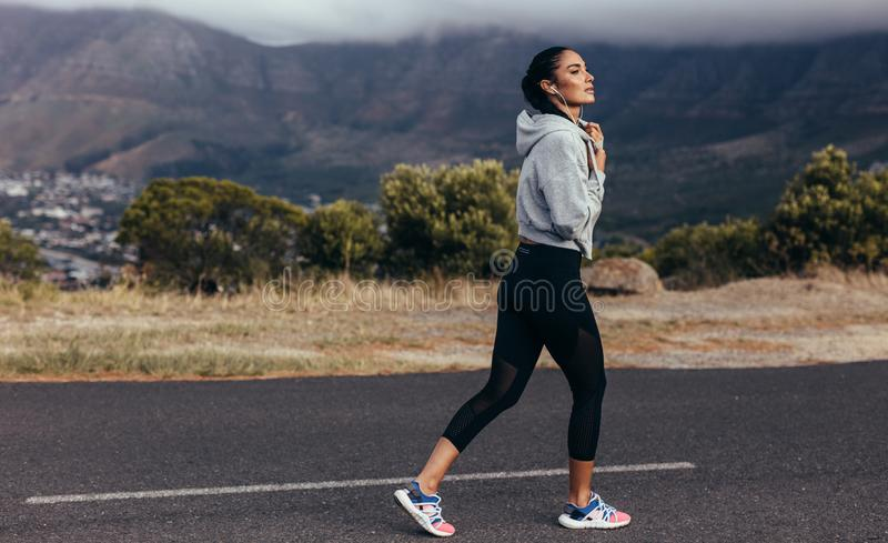 Fitness woman on morning run. Full length of young woman in sportswear jogging on road in morning. Sports woman on morning run royalty free stock photo
