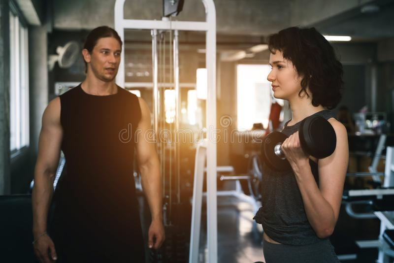 Fitness woman with personal trainer at gym stock photos