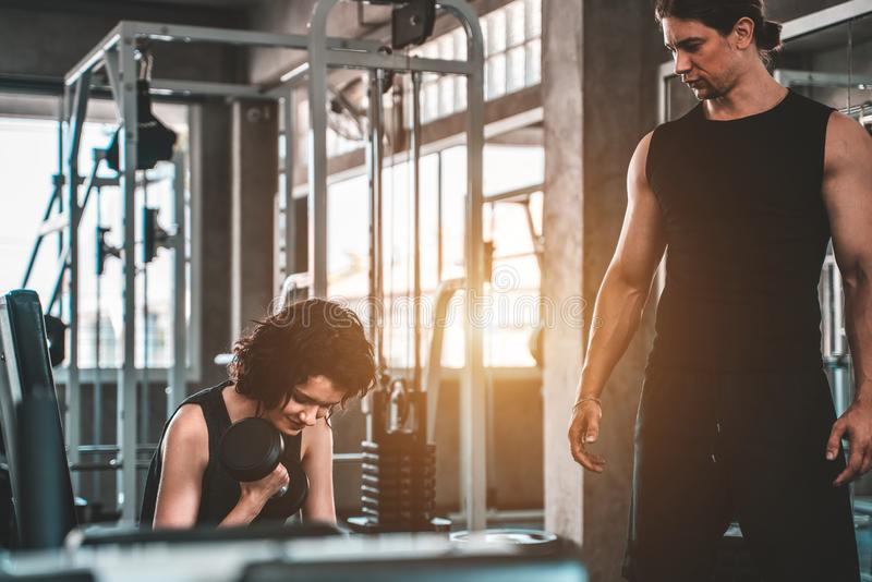 Fitness woman with personal trainer at gym stock image