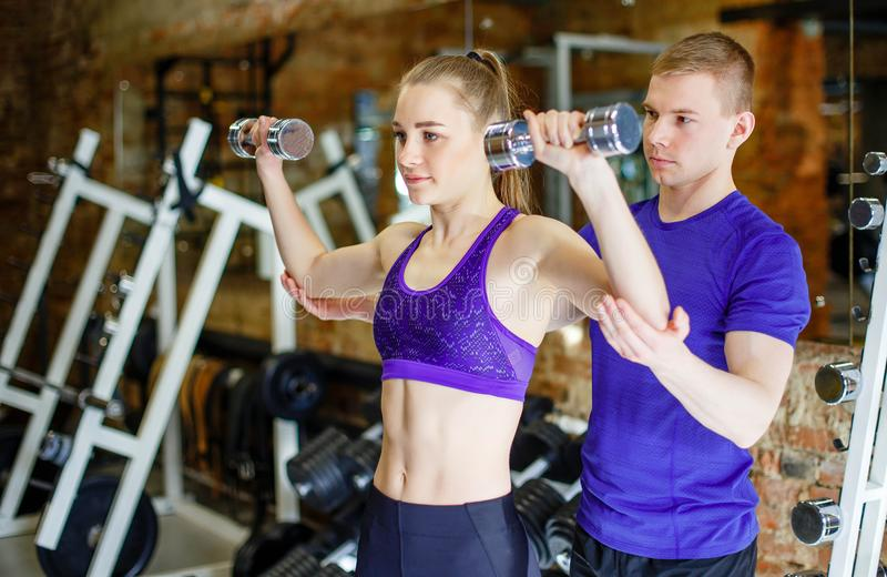 Fitness woman and personal trainer man with weight training equipment. royalty free stock photo