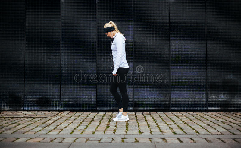 Fitness woman preparing for a city run. Side view of fitness woman preparing for a city run. Young caucasian woman walking on pavement looking down royalty free stock images