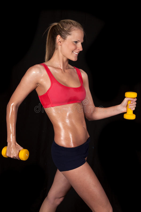 Fitness woman red sports bra weights. A woman with a smile on her face working out with her weights royalty free stock photography
