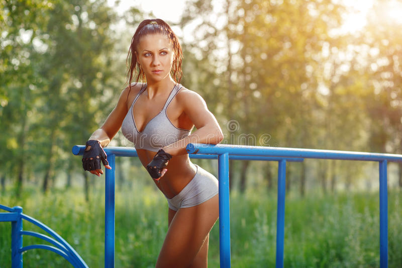 Fitness woman relax after workout exercises on bars outdoor. Brunette fit girl relax after street training royalty free stock photography