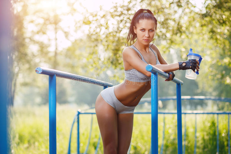 Fitness woman relax after workout exercises on parallel bars. Outdoor with shaker bottle of water. brunette fit girl relax after street training royalty free stock photography
