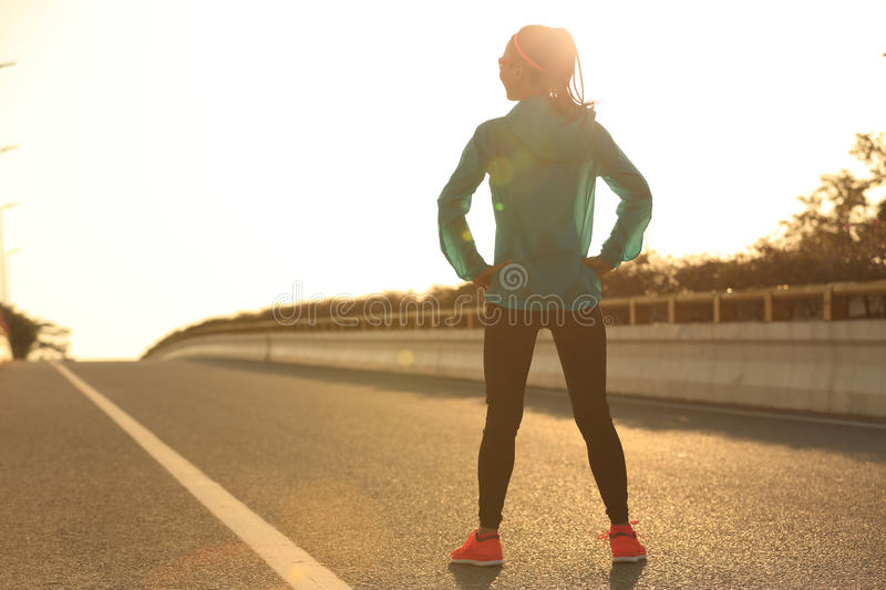 Fitness woman runner athlete standing on sunrise road with her hands on hips stock image