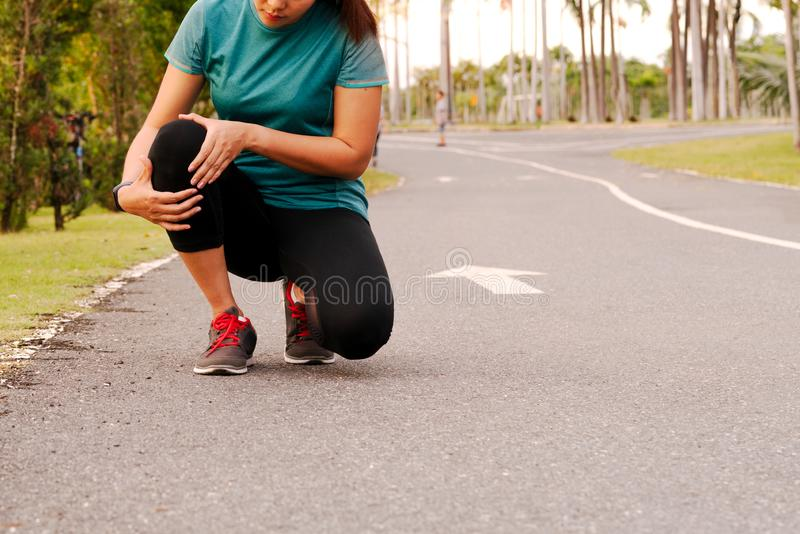 Fitness woman runner feel pain on knee. Outdoor exercise activities concept royalty free stock photography
