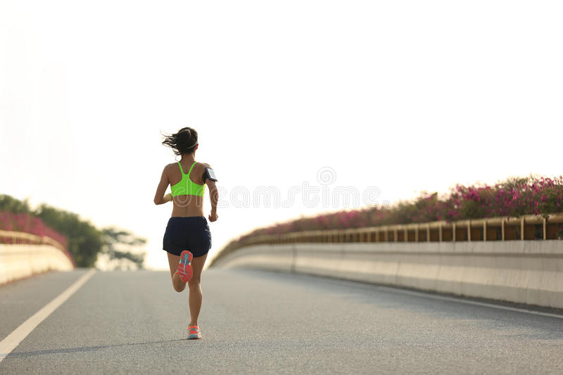 Fitness woman runner running at city road. Young fitness woman runner running at city road stock image