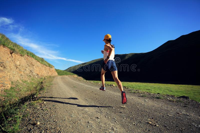 Fitness woman runner running on mountain trail royalty free stock photos