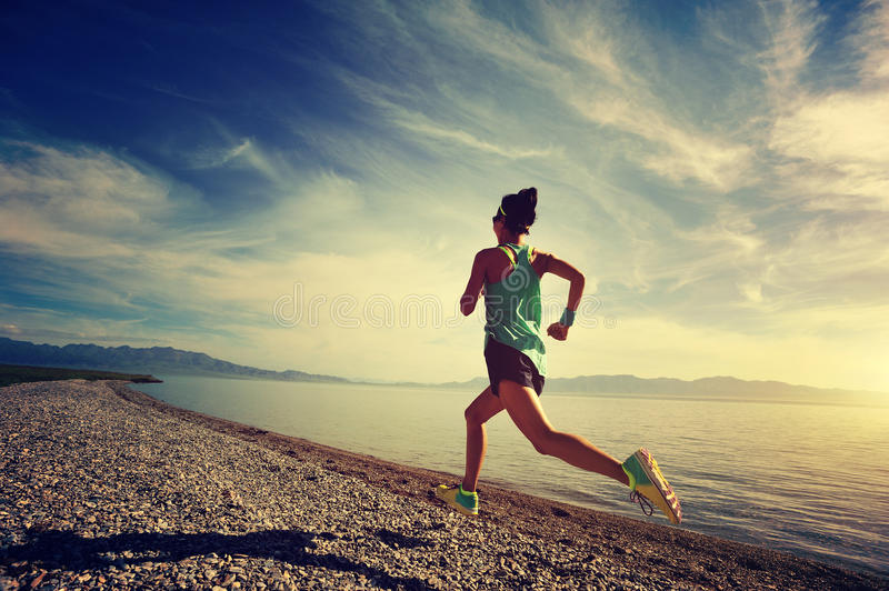 Fitness woman runner running on sunrise seaside trail stock images