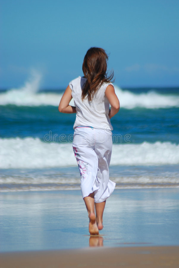 Fitness woman running. Back view of an active caucasian white fitness woman in white clothes running in the sand of the beach towards the blue sea royalty free stock images