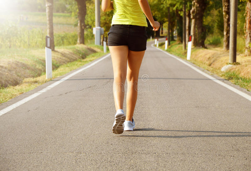 Fitness woman running on asphalt road at sunset stock photography